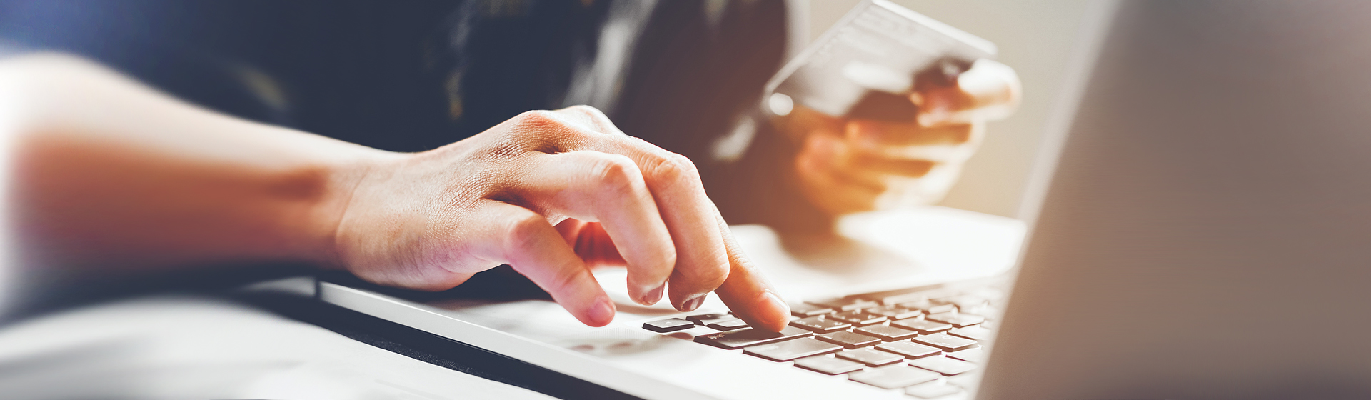 man typing on laptop keyboard and holding credit card